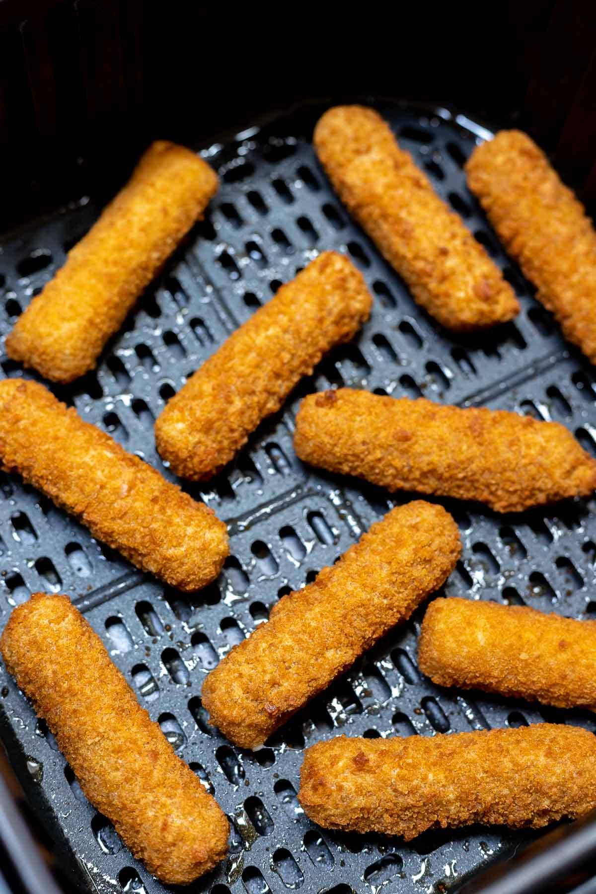 cooked mozzarella cheese sticks in air fryer basket