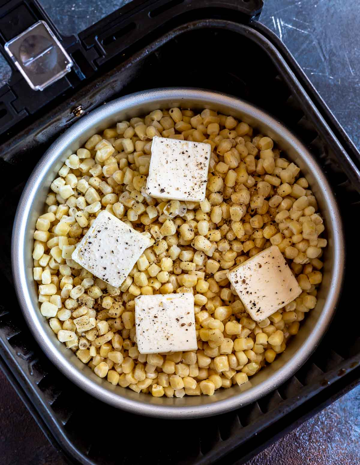 frozen corn and butter slices in pan in air fryer basket