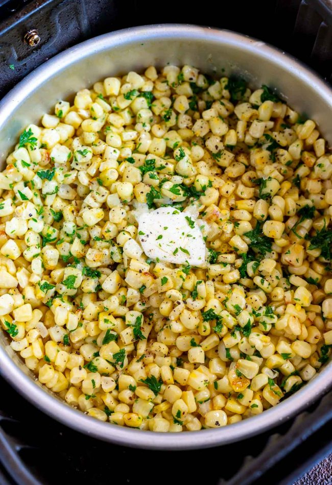 cooked corn with butter and parsley in metal pan