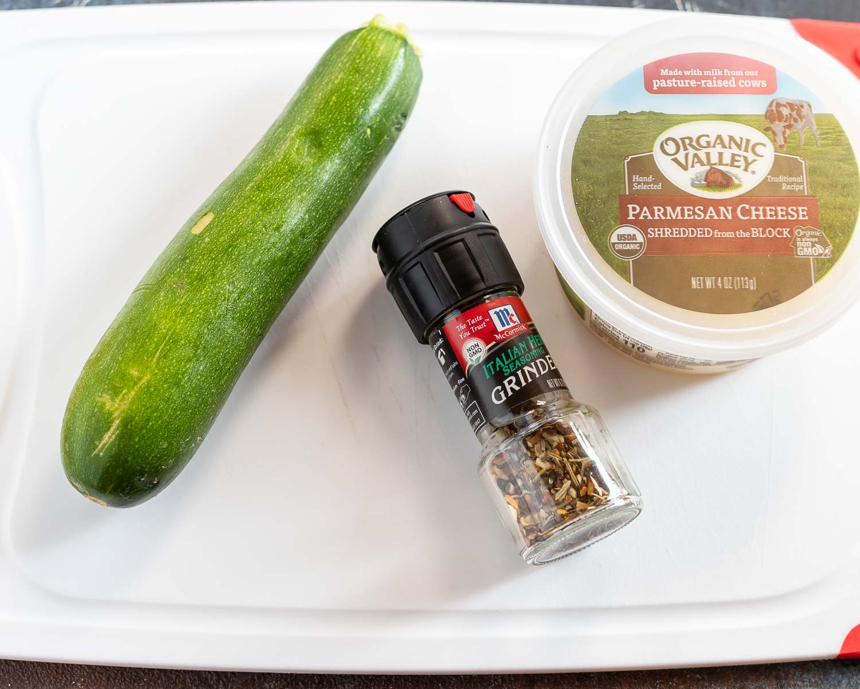zucchini Italian season and tub of parmesan cheese on cutting board