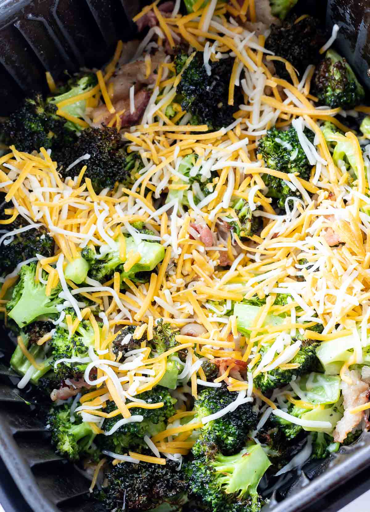 partially cooked broccoli topped with shredded cheese