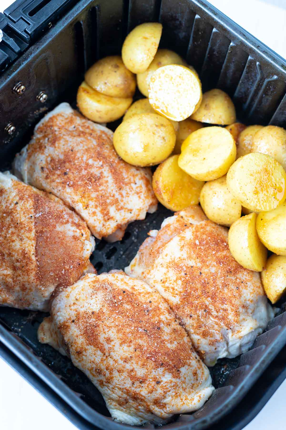 raw chicken and potatoes in air fryer basket