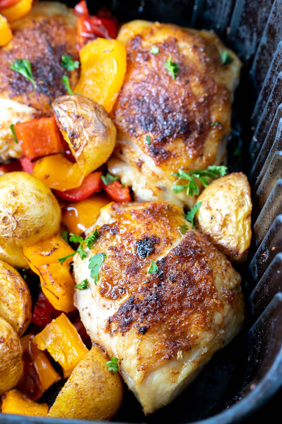 cooked chicken thighs, potatoes and peppers in air fryer basket