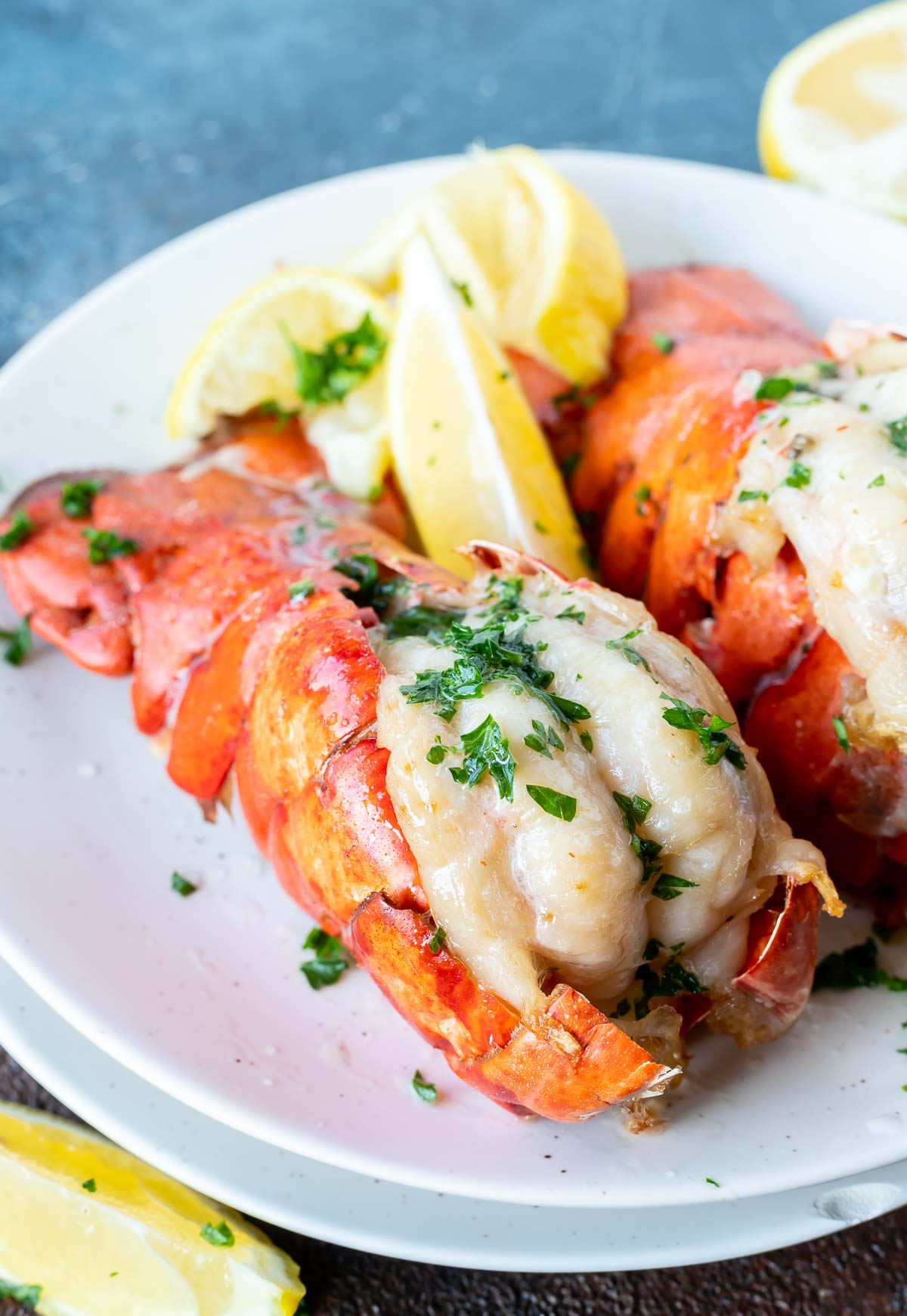 cooked lobster tails and lemon wedges served on white plate