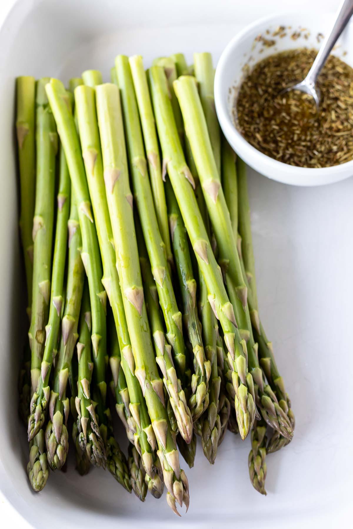 raw asparagus next to oil mixture