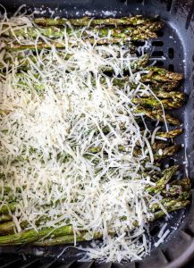 asparagus topped with parmesan in air fryer basket