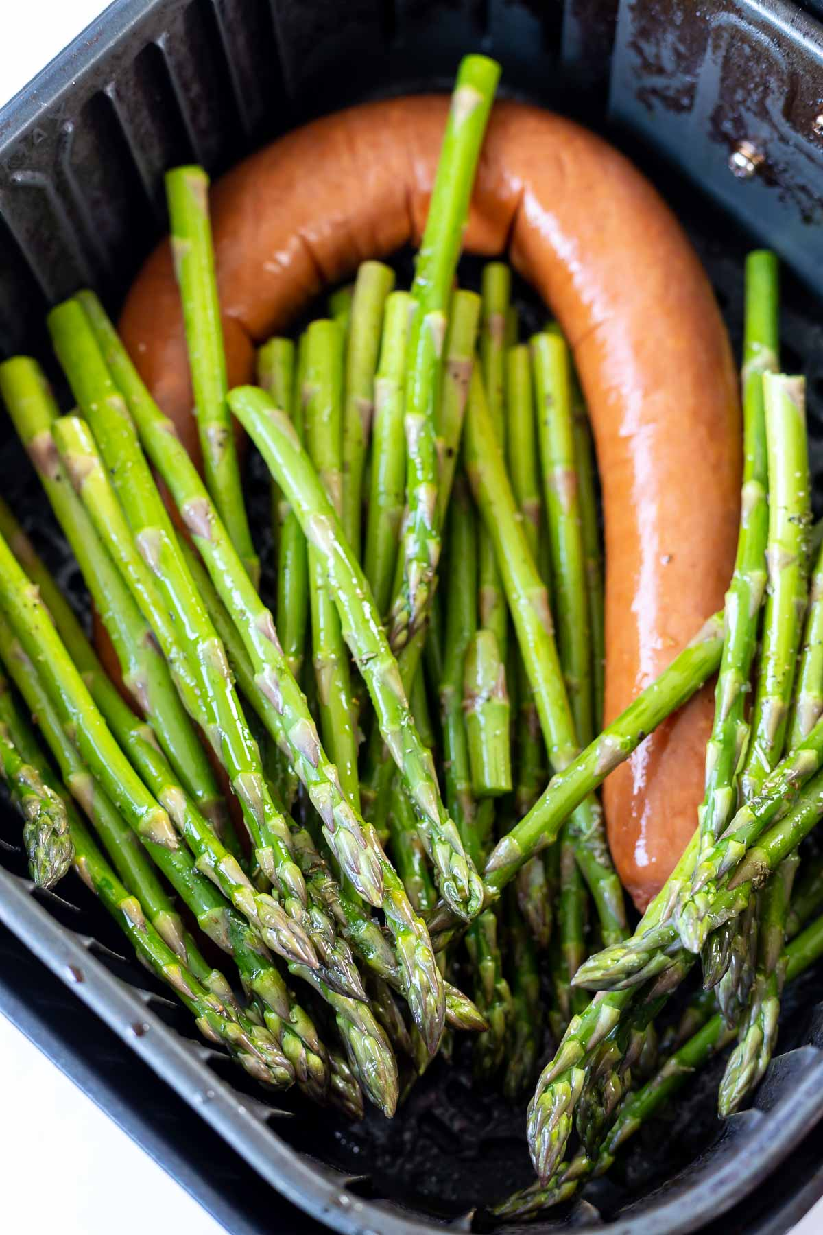 raw sausage and asparagus in air fryer basket