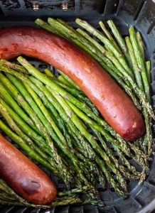 cooked sausage link and asparagus in air fryer basket