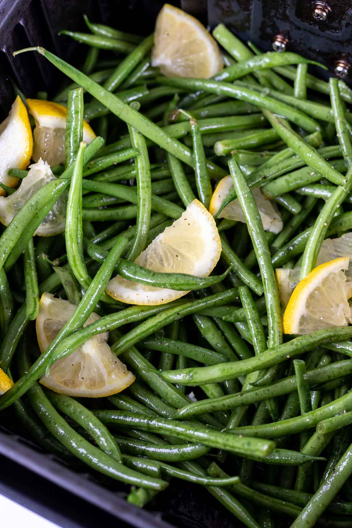 fresh lemons and green beans in air fryer basket