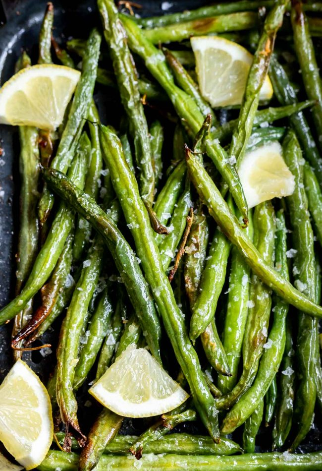 green beans and lemon wedges in air fryer basket