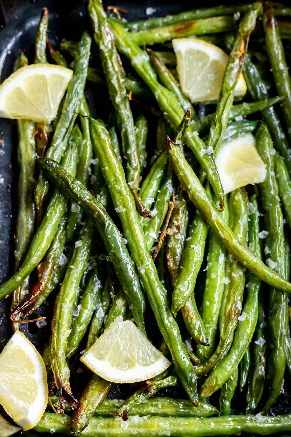 green beans and lemon wedges in air fryer basket