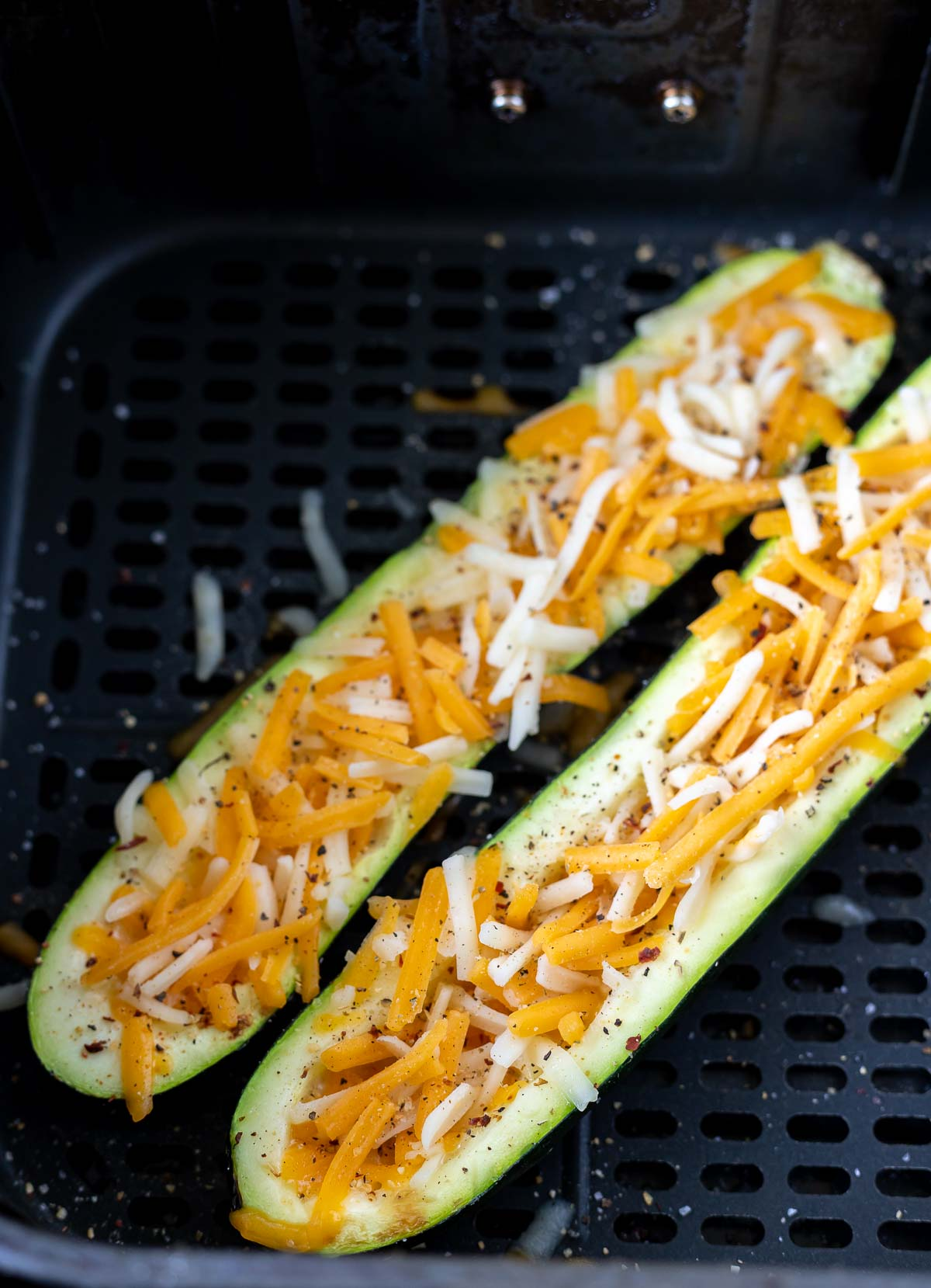 zucchini boats topped with shredded cheese in air fryer basket