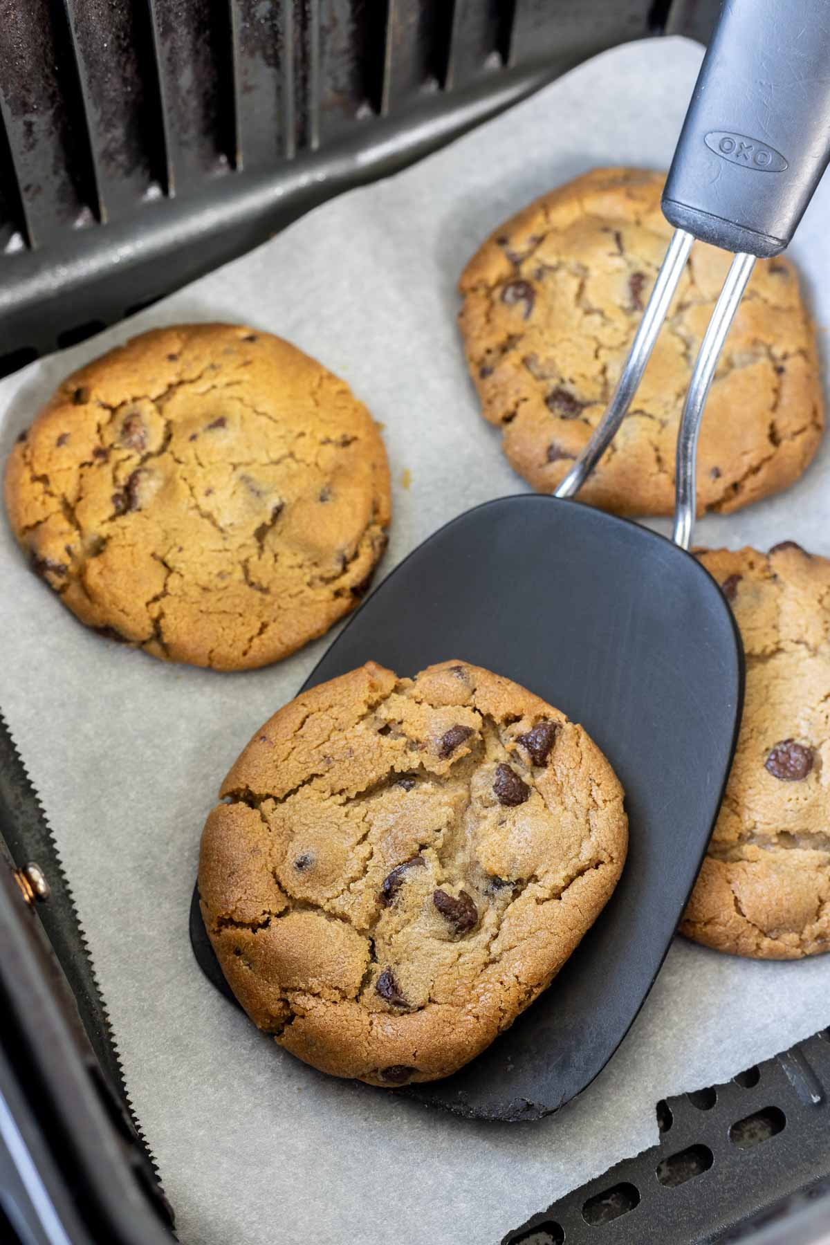 spatula lifting baked cookie out of air fryer basket
