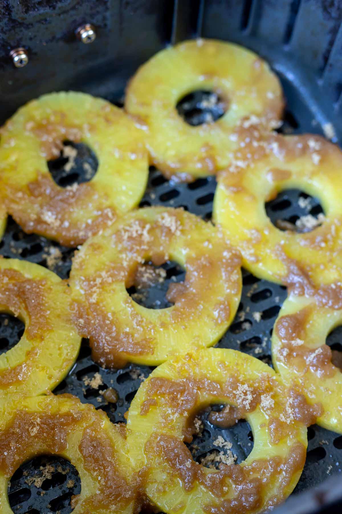 pineapple rings topped with brown sugar in air fryer basket