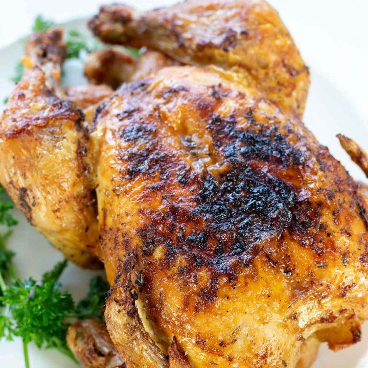 golden roasted chicken on white platter