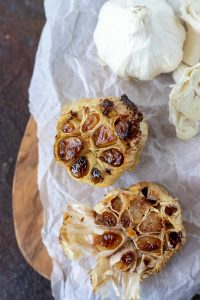 golden brown roasted garlic heads on parchment paper