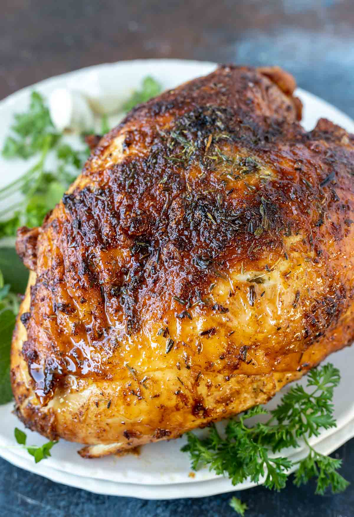 browned roasted turkey breast on white serving platter with herbs