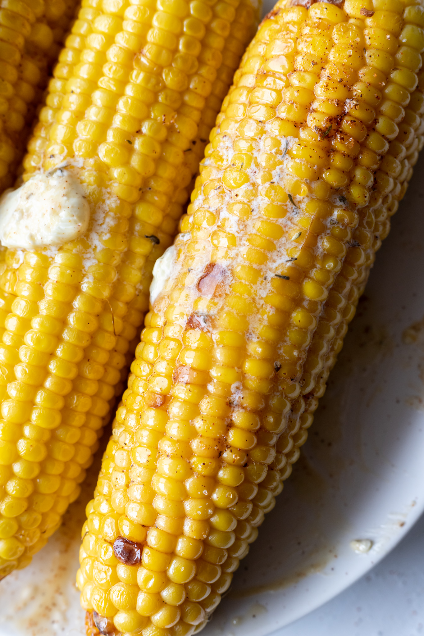 bright yellow corn cobs topped with melted butter