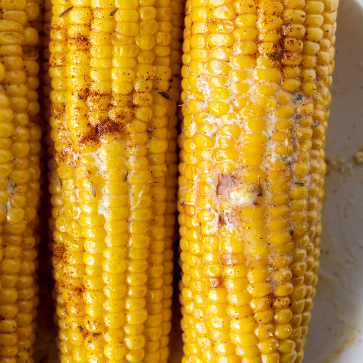cooked buttered corn on the cob on white plate