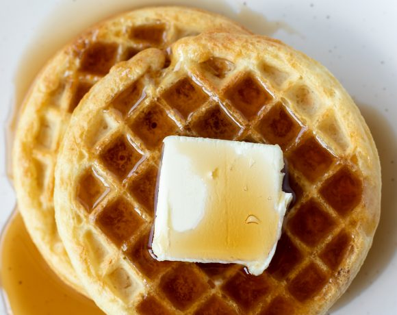 two cooked waffles with syrup and butter on white plate