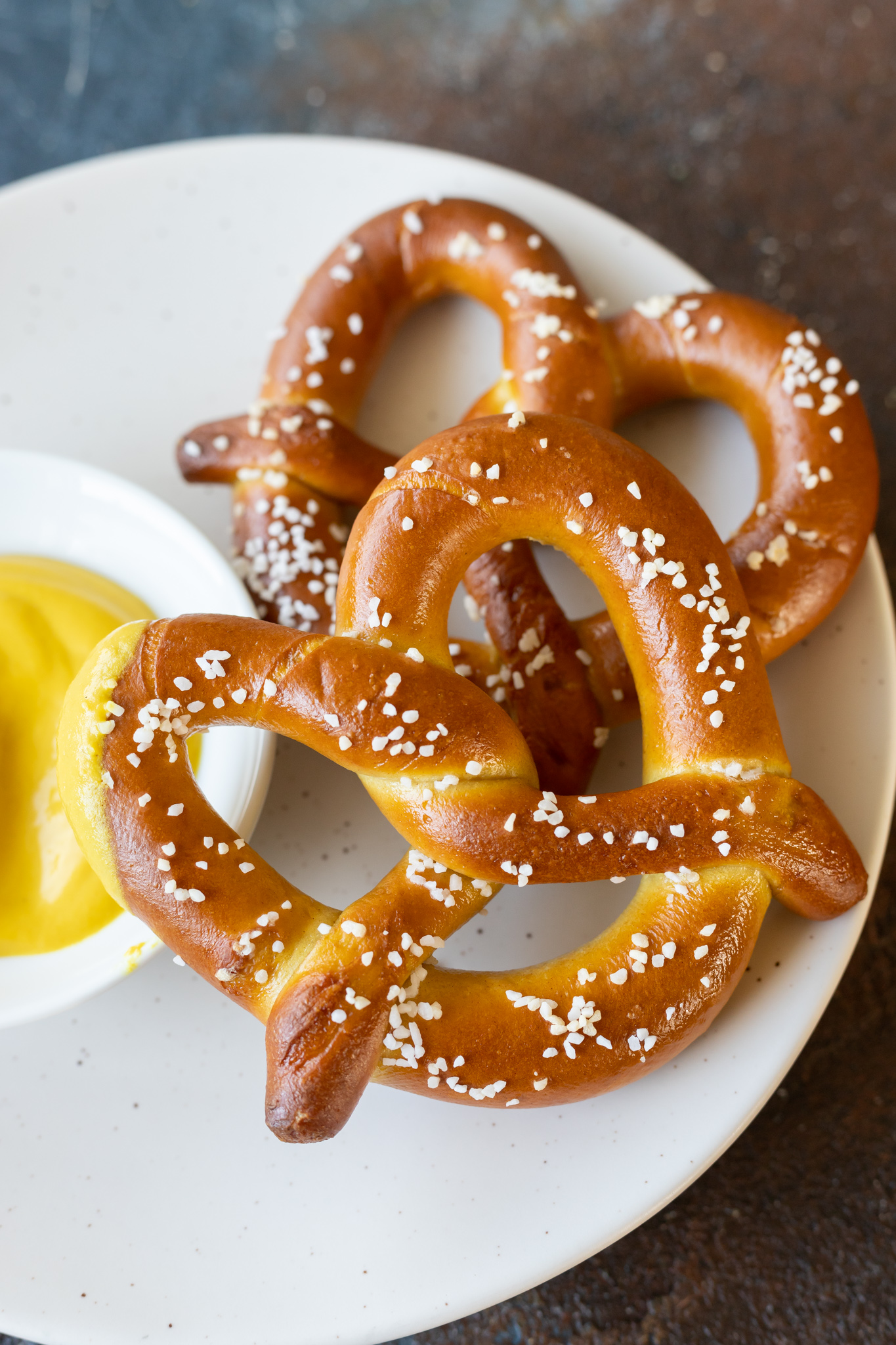 cooked pretzels on white plate next to yellow mustard