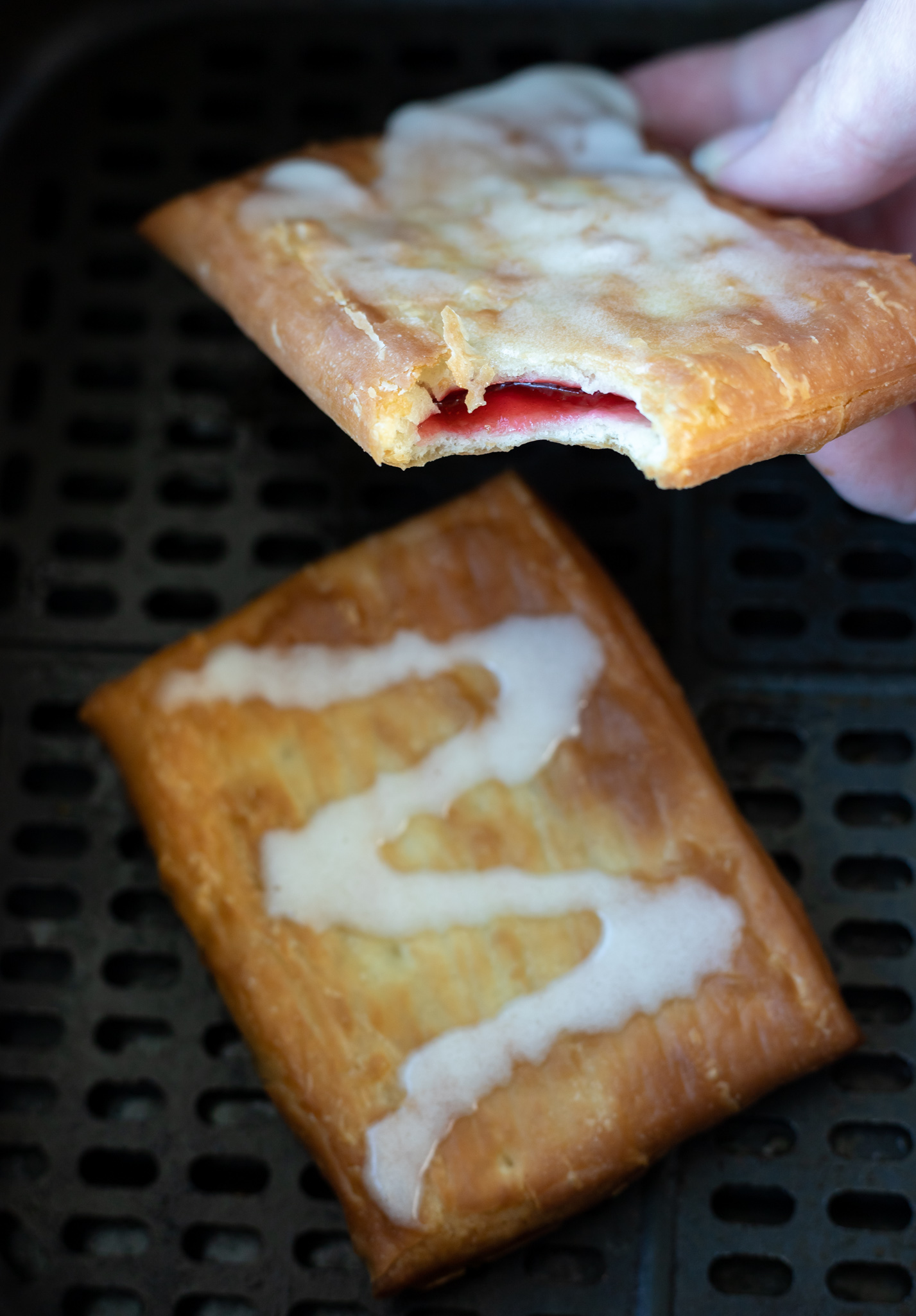 hand holding cooked toaster strudel with bite taken out